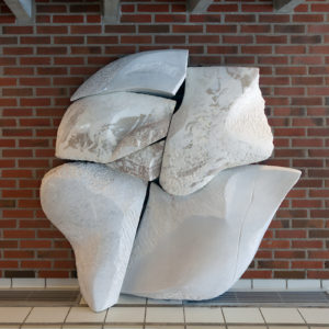 A marble relief by Inger Sitter, which was made originally for the swimming pool at Skådalen School for Deaf and Hearing-Impaired Children, has moved with the school to its new premises. The pale marble, with its many different textures and gently undulating surface, leads one's thoughts to rocky outcrops and stones. These were recurring themes in Sitter's motifs. The new location for the work in the stairwell was chosen as a place where it can be touched by passing children and young people in recognition of the tactile nature of the work.